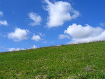 Grassy hill and a beautiful sky. Grassy hill and beautiful clouds in the sky Royalty Free Stock Images