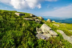 Grassy hill with lots of boulders. Lovely mountainous landscape. fine summer weather Stock Photography