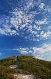 Grassy hill to the road and the sky Royalty Free Stock Images