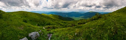 Grassy hillside of Carpathians on overcast day. Gorgeous panorama with rolling hill and mountain ridge in the distance. popular tourist destination - Runa Stock Photo