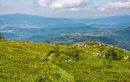 Grassy hillside with huge boulders. Beautiful mountainous landscape on summer morning Royalty Free Stock Photography