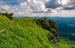 Grassy hillside over the cliff in mountains. Beautiful mountain ridge in the distance. viewing location mountain Pikui. gorgeous landscape of Carpathians Royalty Free Stock Photo