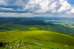 Grassy hillside view from above. Beautiful summer landscape of mountainous area. huge clouds a bright day. rain on the far distant mountain Royalty Free Stock Image