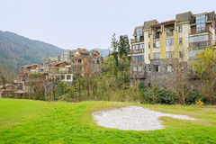 Grassy lawn on slope before houses in mountain Stock Photography