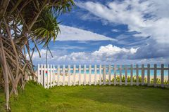 View from a green lawn behind a white fence to the ocean stock photography