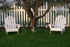 Grassy Lawn and White Lawn Chairs and Picket Fence. Grassy Lawn With White Lawn Chairs and Picket Fence In the Shade Stock Images
