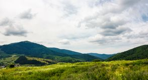 Grassy meadow on a hump in mountains. Lovely summer landscape on an overcast day Stock Images