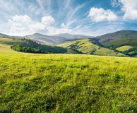 Grassy meadow in mountains. Beautiful summer countryside under the gorgeous sky Stock Photos