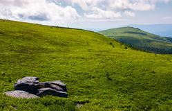 Grassy meadow with peak in a distance. Huge rock on hillside. lovely summer landscape in mountains Royalty Free Stock Photos