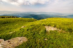 Grassy meadow on top of a hill. Beautiful summer scenery in mountains Royalty Free Stock Photo