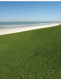 Grassy Ocean View. Grassy field next to a large body of water stock photo