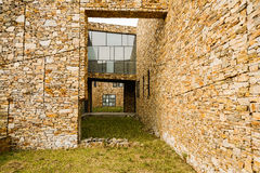 Grassy passageway between buildings with yellow stone surface Royalty Free Stock Photo