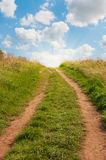 Grassy path facing uphill with blue sky. Stock Images