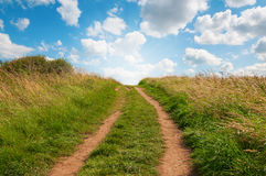 Grassy path facing uphill with blue sky. Royalty Free Stock Photography