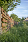 Grassy path goes along a wooden fence to the old house in the vi. Overgrown with high grass path goes along a wooden fence to the old house in the village at Stock Photo