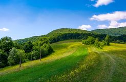 Grassy rural fields on mountain slopes. Country road runs uphill in to the forest. beautiful landscape at the foot of Pikui mountain. fine summer weather with Stock Photo