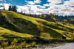 Grassy rural hillside near the village in autumn. Beautiful countryside scenery Royalty Free Stock Image