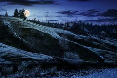 Grassy rural hillside near the village at night. In full moon light. beautiful countryside scenery in autumn Royalty Free Stock Images