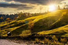 Grassy rural hillside near the village at sunset. Beautiful countryside scenery in autumn Stock Photo