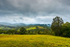 Grassy rural meadow in mountains. Rainy september weather. distant ridge in clouds and haze Royalty Free Stock Image