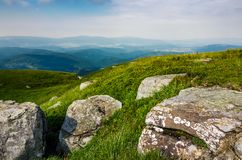Grassy slope of a hill with huge boulders. Beautiful landscape of Polonina Runa ridge on a cloudy summer day Royalty Free Stock Photography