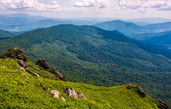Grassy slope with huge boulders. View to valley with forested hills on fine summer day Stock Photo