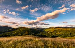 Grassy slope in mountainous countryside at sunset. Beautiful landscape with gorgeous cloudscape over the hills of Carpathian mountains. location Nyzhni Vorota Royalty Free Stock Photos