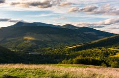 Grassy slope in mountainous countryside at sunset. Beautiful landscape with gorgeous cloudscape over the hills of Carpathian mountains. location Nyzhni Vorota Stock Images