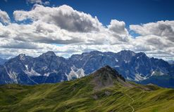 Grassy slopes of Carnic Alps with cliffs of Sexten Dolomites Stock Images