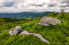 Grassy slopes of Carpathian mountains. Huge boulder on the edge of a hill side. mountain ridge under the cloudy sky in summer time Royalty Free Stock Photography