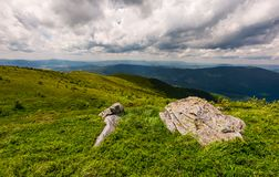 Grassy slopes of Carpathian mountains. Huge boulder on the edge of a hill side. mountain ridge under the cloudy sky in summer time Stock Photo