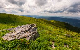 Grassy slopes of Carpathian mountains. Huge boulder on the edge of a hill side. mountain ridge under the cloudy sky in summer time Royalty Free Stock Images