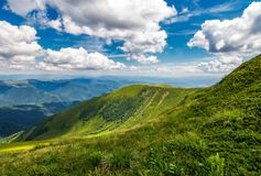 Grassy slopes under the beautiful cloudscape. Gorgeous summer landscape in mountains royalty free stock photo