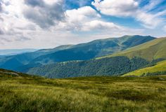 Grassy slopes under the cloudy sky. Grassy slopes of mountain ridge under the cloudy sky. gorgeous summer nature scenery Royalty Free Stock Photo