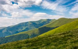 Grassy slopes under the cloudy sky. Grassy slopes of mountain ridge under the cloudy sky. gorgeous summer nature scenery Stock Photography
