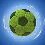 Grassy soccerball. 3D illustration over round blue sky Royalty Free Stock Images