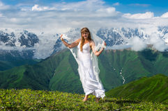 Grassy valley and beautiful dancing girl in white wedding dress Stock Image