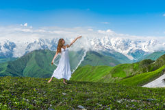 Grassy valley and beautiful dancing girl in white wedding dress Royalty Free Stock Photos