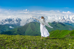Grassy valley and beautiful dancing girl in white wedding dress Royalty Free Stock Image