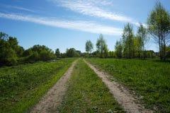 Grasweg met de lentehemel met wolken royalty-vrije stock afbeeldingen