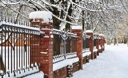 Grata del recinto con le colonne del mattone in neve Immagine Stock Libera da Diritti