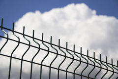Grate. A detail of a grate with a blue sky and white cloud in the background stock photo