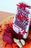 Grate the beets on a grater, beets and garlic rubbed on a grater, red beetroot and garlic, chop on a grater royalty free stock photography