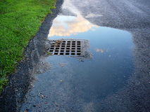 Grate Cover. The Grate Cover caught my eye, after the rain, with a nice little puddle with a reflection of the sky.  This photo was taken in Seekonk Royalty Free Stock Photos