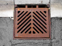 Grate covering a storm sewer drain. Rusted metal square grate over a storm sewer drain on the street next to the curb royalty free stock photo