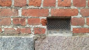 Grate. In old red brick wall Royalty Free Stock Photography