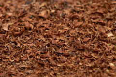 Grated 100 percent cacao dark chocolate background. Full-frame, shallow DOF Stock Images