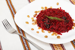 Grated beet salad with prunes and raisins, served on a white pla Royalty Free Stock Photo