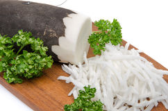 Grated black radish on a wooden board Stock Image