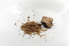 Grated black truffle. On white plate Stock Image